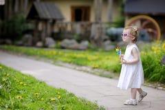 Enfant en bas âge drôle dans la fille de lunettes de soleil avec un jouet Images libres de droits