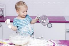 Enfant en bas âge drôle sur la cuisine jouant avec de la farine Image stock