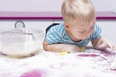 Enfant en bas âge drôle sur la cuisine jouant avec de la farine Photos libres de droits
