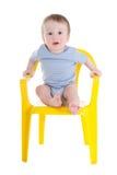 Enfant en bas âge drôle de bébé garçon s'asseyant sur peu de chaise d'isolement sur le blanc Photographie stock libre de droits