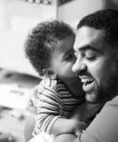 Enfant en bas âge embrassant sa gamme de gris de père Photo stock