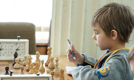 Enfant en bas âge entreprenant une démarche avec un cheval pendant un tournoi d'échecs à une école, avec plusieurs autres concurr Photos libres de droits