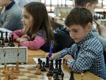 Enfant en bas âge entreprenant une démarche avec un cheval pendant un tournoi d'échecs à une école, avec plusieurs autres concurr Image stock