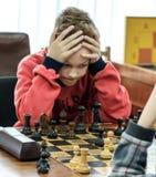 Enfant en bas âge entreprenant une démarche avec un cheval pendant un tournoi d'échecs à une école, avec plusieurs autres concurr Photographie stock
