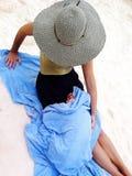 Enfant en bas âge enveloppé dans une serviette sur la plage photos stock