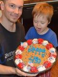 Enfant en bas âge et papa avec le biscuit géant de Jour de la Déclaration d'Indépendance Images libres de droits