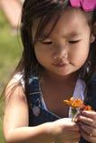 Enfant en bas âge féminin jouant avec la fleur dehors Photo stock