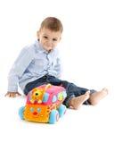Enfant en bas âge heureux avec le véhicule coloré de jouet Photo stock