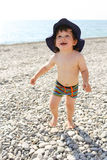Enfant en bas âge heureux courant le long de la plage de cailloux Photos libres de droits