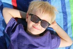 Enfant en bas âge heureux détendant sur la serviette de plage avec des lunettes de soleil Images libres de droits