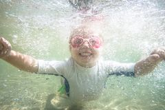 Enfant en bas âge heureux d'enfant nageant sous l'eau pendant des vacances de vacances de plage d'été images libres de droits