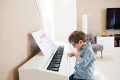 Enfant en bas âge heureux jouant le piano images libres de droits