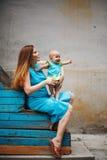 Enfant en bas âge heureux mignon s'asseyant sur les genoux affectueux du ` s de mère Photographie stock libre de droits