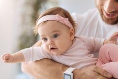 Enfant en bas âge impliqué se situant dans les bras du jeune père Image stock