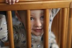 Enfant en bas âge jetant un coup d'oeil par la huche photos stock