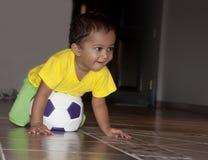 Enfant en bas âge jouant au football Photo stock