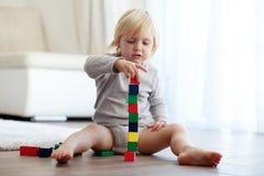 Enfant en bas âge jouant avec les blocs en bois Images stock