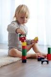 Enfant en bas âge jouant avec les blocs en bois Photos stock