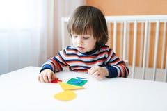 Enfant en bas âge jouant avec les chiffres géométriques Photo libre de droits