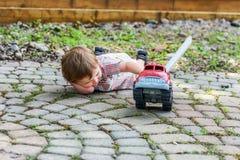 Enfant en bas âge jouant avec Toy Fire Truck Outside - série 8 images libres de droits