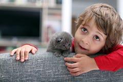 Enfant en bas âge jouant avec un chaton Photo stock