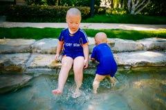 Enfant en bas âge jouant dehors dans le courant Image stock