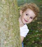 Enfant en bas âge jouant le cache-cache en parc, se cachant derrière un arbre. Très assez. Image libre de droits