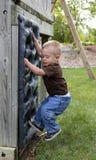 Enfant en bas âge jouant sur le mur s'élevant Photo libre de droits
