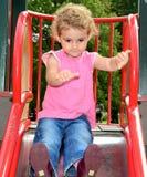 Enfant en bas âge jouant sur une glissière au terrain de jeu. Photo libre de droits