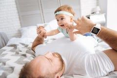 Enfant en bas âge joyeux se trouvant sur son père dans la chambre à coucher Image libre de droits