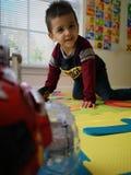 Enfant en bas âge lisant, jouant et apprenant à la maison le livre d'ABC photos stock