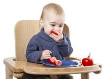 Enfant en bas âge mangeant dans la chaise d'arbitre Image libre de droits