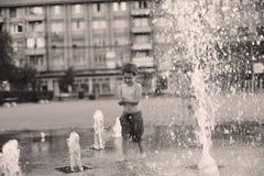 Enfant en bas âge marchant dans une fontaine d'eau de éclaboussement Photo stock