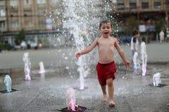 Enfant en bas âge marchant dans une fontaine d'eau de éclaboussement Image stock