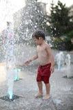 Enfant en bas âge marchant dans une fontaine d'eau de éclaboussement Image libre de droits
