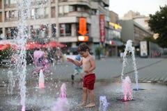 Enfant en bas âge marchant dans une fontaine d'eau de éclaboussement Photo libre de droits
