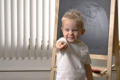 Enfant en bas âge mignon de petit garçon, deux années Dessin sur le chalkbo photo stock