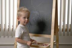 Enfant en bas âge mignon de petit garçon, deux années Dessin sur le chalkbo photos stock