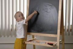 Enfant en bas âge mignon de petit garçon, deux années Dessin sur le chalkbo image libre de droits