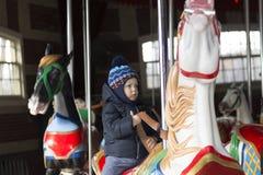 Enfant en bas âge mignon heureux dans des vêtements chauds montant le cheval de carrousel pendant le voyage de famille à New York photographie stock
