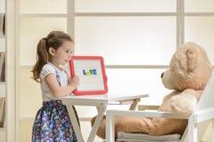 Enfant en bas âge mignon jouant le jeu de rôle de professeur avec son jouet Photographie stock