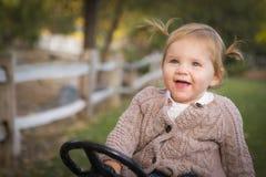 Enfant en bas âge mignon riant et jouant sur Toy Tractor Outside Images libres de droits