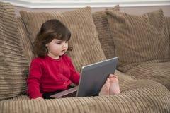 Enfant en bas âge observant les bandes dessinées en ligne Images libres de droits