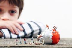 Enfant en bas âge observant les personnes miniatures casser un oeuf image stock