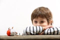 Enfant en bas âge observant les personnes miniatures casser un oeuf images stock