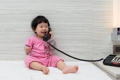 Enfant en bas âge parlant au téléphone image stock