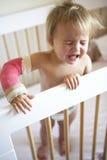 Enfant en bas âge pleurant avec le bras dans le moulage Photo stock