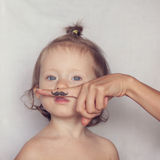 Enfant en bas âge posant avec la moustache de hippie Photographie stock libre de droits