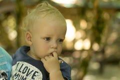 Enfant en bas âge réfléchi aux yeux bleus mignon Fond brouillé Enfant en bas âge méditatif dans t-court avec la maman d'amour du  Photographie stock libre de droits