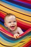 Enfant en bas âge riant balançant dans une oscillation de sécurité Photos libres de droits